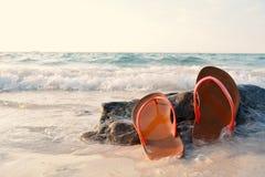 Sandália vermelha no fundo da rocha e do mar Imagem de Stock