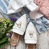 Sandálias brancas com flores em um fundo de madeira imagem de stock royalty free