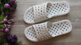 Sandálias brancas do chuveiro/que secam rapidamente deslizadores e flores do banho fotos de stock