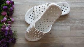 Sandálias brancas do chuveiro/que secam rapidamente deslizadores e flores do banho fotos de stock royalty free