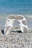 Sandálias brancas na praia Imagem de Stock Royalty Free