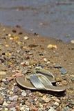 Sandálias brilhantes do ouro das mulheres na praia Fotografia de Stock Royalty Free