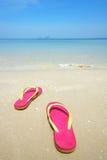Sandálias cor-de-rosa na praia bonita Foto de Stock Royalty Free
