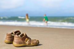 Sandálias da criança com menino e a menina borrados Fotografia de Stock Royalty Free