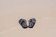 Sandálias da praia em uma praia arenosa Imagem de Stock Royalty Free