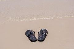 Sandálias da praia em uma praia arenosa Fotos de Stock Royalty Free
