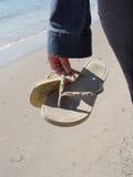 Sandálias da terra arrendada da mulher fotografia de stock