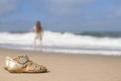 Sandálias das meninas na areia na praia Imagens de Stock Royalty Free