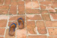 Sandálias de borracha marrons velhas no assoalho do tijolo Foto de Stock Royalty Free