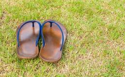 Sandálias de borracha marrons velhas no campo de grama Fotografia de Stock