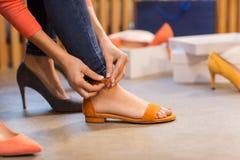 Sandálias de tentativa da jovem mulher na sapataria fotos de stock royalty free