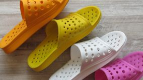 Sandálias do chuveiro alaranjado, amarelo, branco e cor-de-rosa/que secam rapidamente deslizadores do banho fotografia de stock