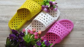 Sandálias do chuveiro amarelo, branco e cor-de-rosa/que secam rapidamente deslizadores e flores do banho imagens de stock