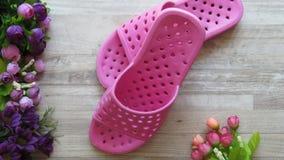 Sandálias do chuveiro cor-de-rosa/que secam rapidamente deslizadores e flores do banho imagens de stock royalty free