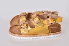 Sandálias douradas das crianças isoladas no fundo branco imagem de stock royalty free