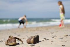 Sandálias e crianças das crianças na praia Foto de Stock