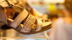 Sandálias na fileira na prateleira da loja Fotografia de Stock