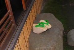 Sandálias verdes do Geta na pedra na casa japonesa foto de stock royalty free