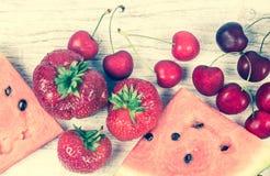 Sandía, fresas y cerezas en fondo de madera Fotos de archivo