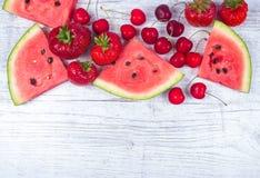 Sandía, fresas y cerezas en fondo de madera Imagen de archivo libre de regalías