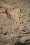 Sand. Girl pouring fine sand from two hand on beach Royalty Free Stock Image