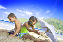 Among the sand. Portrait of little kids having good time in summer environment Stock Photos