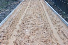 Sand als Basis, bevor die Pflastersteine gelegt werden, zerstreut von den Arbeitskräften, die Schaufeln verwenden und tamped mit  stockfotografie