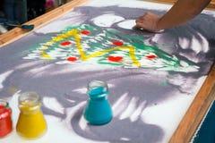 Sand animation, drawing sand closeup, girl draws a Christmas tree on the sand Royalty Free Stock Image