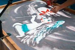 Sand animation, drawing sand closeup, girl drawing an angel on the sand Stock Photo