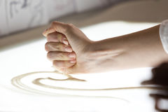 Sand animation. The girl's arm, drawing sand Stock Photos