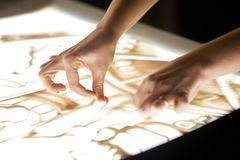 Sand animation. The girl`s arm, drawing sand closeup royalty free stock image
