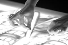Sand animation. The girl`s arm, drawing sand closeup In black and white royalty free stock photography