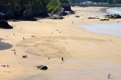 Sand art at Tolcarne Beach, Newquay. Sand art being created at Tolcarne Beach in Newquay, Cornwall Stock Image