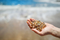 Sand av den glass stranden nära den portAllen staden på Kauai Arkivbild