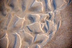 Sand av en strand med modeller royaltyfria bilder