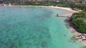 Sand Bach in Mauritius Fliegen mit Brummen über dem Indischen Ozean und den Leuten stock footage