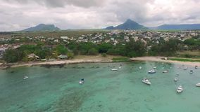 Sand Bach in Mauritius. Flying with drone over the Indian Ocean and people. Luxury yacht and boats on coastline stock video