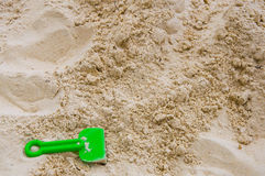 Sand background with green beach toy Stock Photography