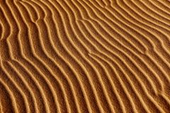 Sand background with a natural wavy pattern. Closeup of a sand background with a natural wavy pattern Stock Photo