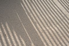 Sand background pattern with shadows. Close-up of beach sand with daigonal grafic shadows lines background Stock Photos