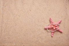 Sand Background with Pink starfish and pearls Royalty Free Stock Images