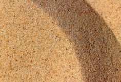 Sand background texture. One side of the sand dune is illuminated by the sun, the side of the dune in the shade is the dark side Stock Photos