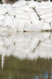 Sand bags and flood water Stock Photography