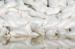 Sand bags and flood water Stock Image