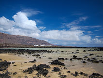 Sand banks with volcanic stones on the coast of the Atlantic Ocean. Deep blue sky with white clouds. Mountains and volcanoes on th Royalty Free Stock Image