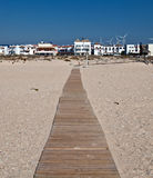 Sand beach. Path of wooden planks next to the sand beach located in the Spanish town of Zahara, a clear day, you see  a group of houses with windmills Royalty Free Stock Image