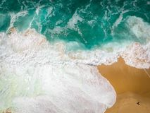 Sand beach aerial, top view of a beautiful sandy beach aerial shot with the blue waves rolling into the shore royalty free stock photo
