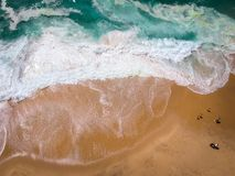 Sand beach aerial, top view of a beautiful sandy beach aerial shot with the blue waves rolling into the shore royalty free stock photos