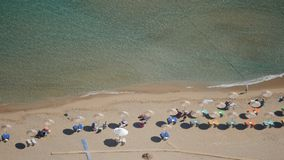 Sand beach from aerial top view. Tourists relaxing, umbrellas and deck chairs on the beach. Rhodes beach stock footage