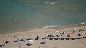 Sand beach from aerial top view. Tourists relaxing, umbrellas and deck chairs on the beach. Rhodes beach stock video footage